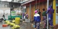 15日白天,广东湛江风雨逐渐明显,市民正在加固门窗。(图/殷美祥) - News.Sina.com.Cn